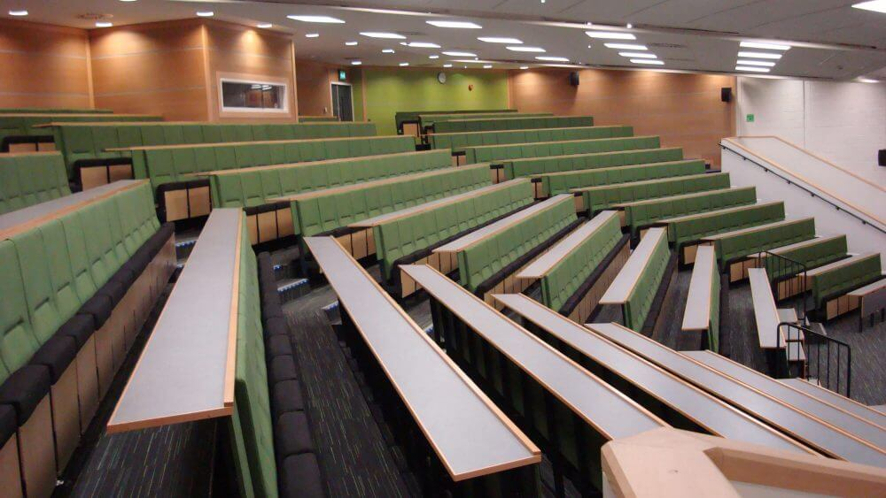 Lecture theatre, green chairs, writing desks