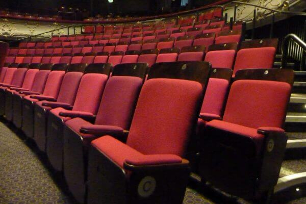 Red raked theatre seating, wooden backs