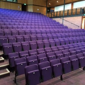 Wide view of retractable seating unit with purple theatre chairs with no arm-rests