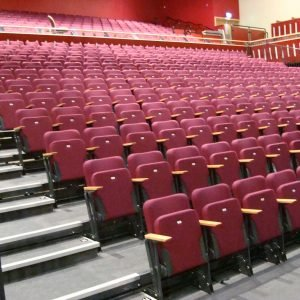 View of all rows of maroon chairs with light wood arm-rests