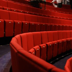Two rows of red theatre seating with no arm-rests