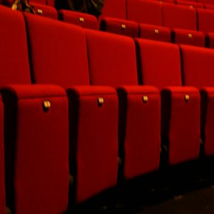 Row of red theatre seats with no arm-rests