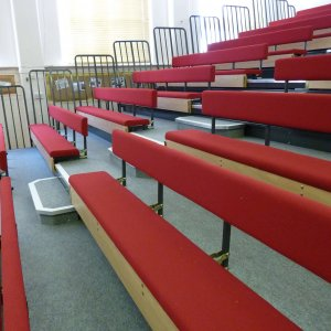 red bench seating retractable to sit flush against walls in sports or lecture halls