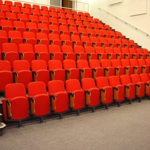 Lecture theatre, red chairs, folding writing tablet