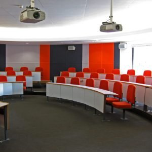 Red seats, white writing desks, lecture theatre seating