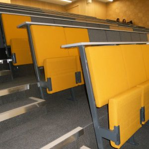 Yellow and grey lecture chairs, white writing desks, fixed tiering