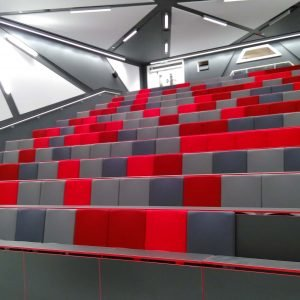Multi-coloured lecture theatre seats, writing desks