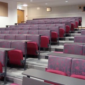 Purple and grey lecture theatre chairs, black writing desks