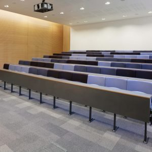 Small lecture theatre, purple, blue and black chairs, writing desks