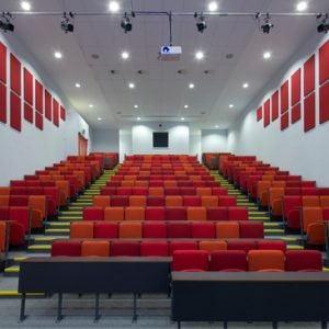 lecture theatre with red and orange seats and dark writing desks