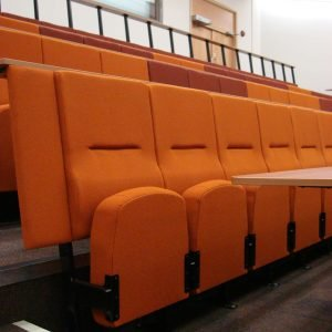 Orange, high-backed lecture theatre chairs, writing desks