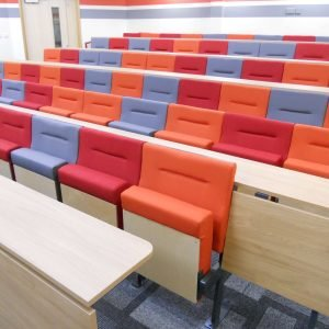 Red, orange, and blue lecture theatre chairs with wooden writing desks
