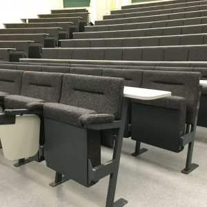 Rows of black lecture theatre chairs with fold-down writing tablets